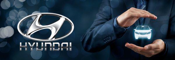 A Hyundai logo next to a man with his hands around a car graphic