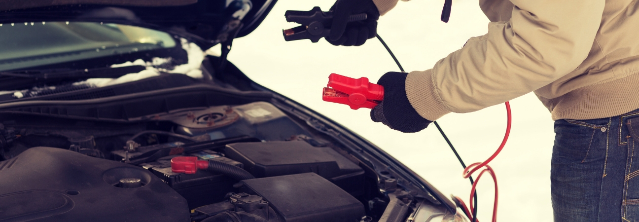 A man trying to jumpstart a car battery in the snow featured in a blog post about car maintenance