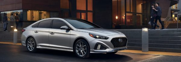 Gray 2019 Hyundai Sonata parked on a city street in front of a theater.
