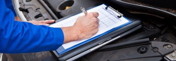 Service technician going through car maintenance checklist
