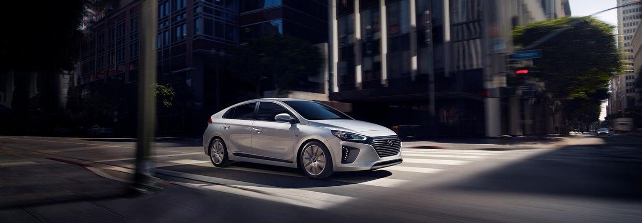Silver 2019 Hyundai IONIQ Hybrid driving through intersection